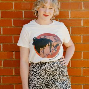 Image shows woman smiling in Artemis tee in Natural