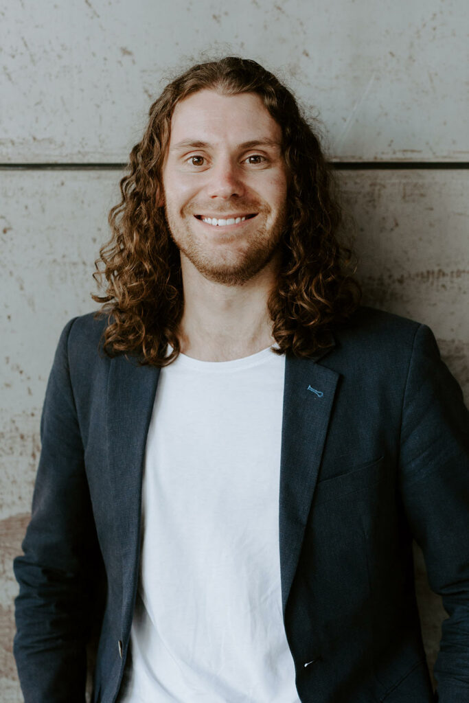 Image shows Jono Naef in a black blazer and white tshirt smiling toward the camera